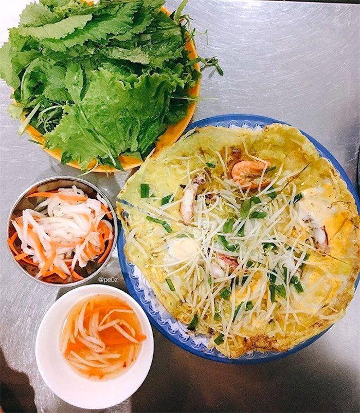 Bánh xèo chảo ăn kèm với các loại rau sống, dưa chua và nước mắm chua ngọt